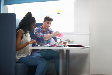Young female and male college students planning with adhesive notes