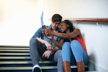 Young college student couple reading smartphone texts on stairway