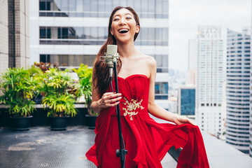 Asian woman smiling and singing on rooftop in urban city