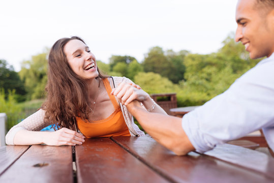 Young couple arm wrestling on picnic bench laughing