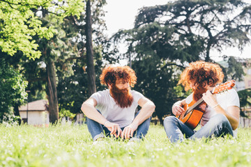 Young male hipster twins with red beards sitting in park playing guitar