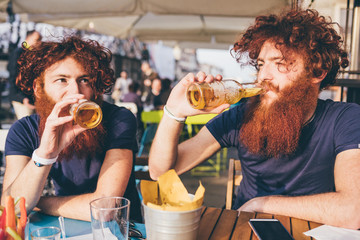 Hipster twins drinking beer at sidewalk cafe