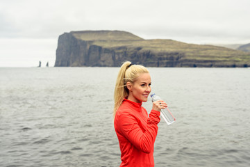 Runner drinking water near ocean, Tjornuvik, Faroe Islands