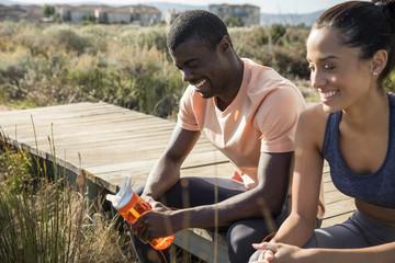 Couple in sportswear sitting on boardwalk