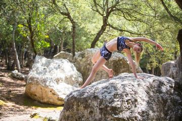 Woman on rock bending backwards stretching