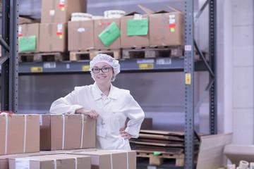 Factory worker in storeroom wearing hair net looking at camera smiling
