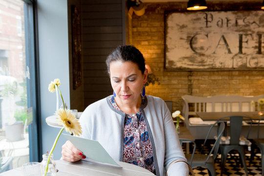 Mature female customer reading menu in cafe