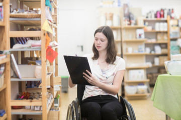 Young female shop assistant using wheelchair stocktaking in shop