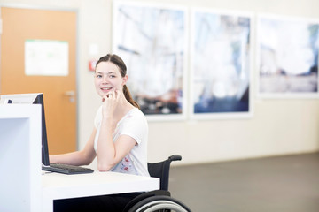Young female university student using wheelchair using computer at desk
