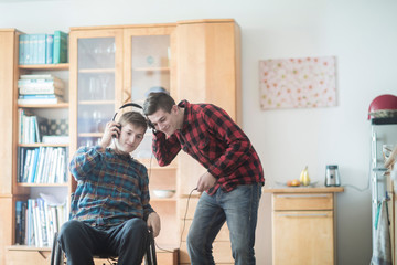 Young man using wheelchair listening to headphone music with friend in kitchen