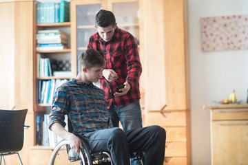 Young man using wheelchair reading smartphone texts with friend in kitchen