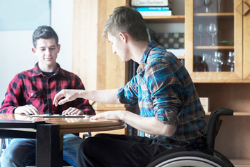 Young man using wheelchair playing draughts with friend in kitchen