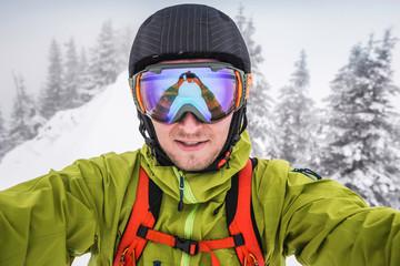 Close up of male skier wearing ski goggles taking selfie on mountain at Kranzegg, Bavaria, Germany