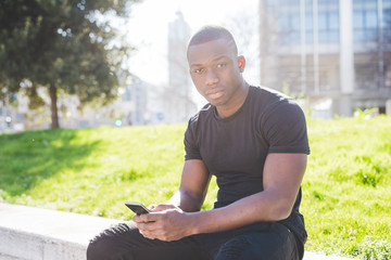 Portrait of young man, sitting outdoors, holding smartphone