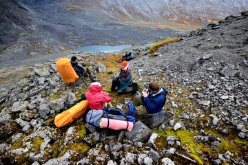 Four adult hikers taking a break in rugged valley landscape, Khibiny mountains, Kola Peninsula, Russia