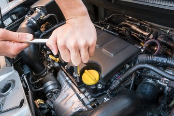 Hands repairing a modern car engine with a wrench