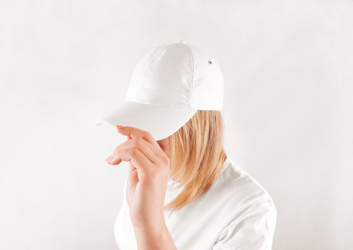 Blank white baseball cap mockup template, wear on women head, isolated, side view. Woman in clear hat and t shirt uniform mock up holding visor of caps. Cotton basebal cap design on delivery guy.