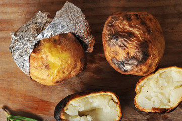 potatoes baked in foil on a wooden background