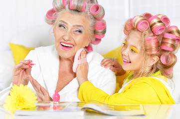 Senior woman and granddaughter doing make up