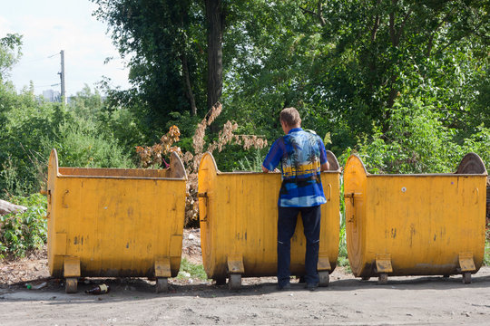 Homeless digs in yellow dumpsters in the city
