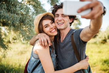 Couple with backpacks hiking in the forest and making selfie