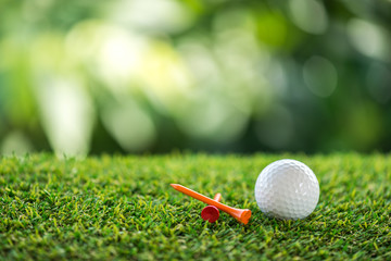 golf ball and wooden tee on grass