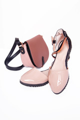 Women's beige sandals and handbag on a white background