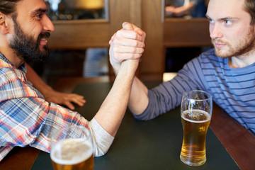 happy male friends arm wrestling at bar or pub