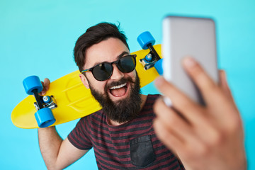 young handsome bearded hipster man makes selfie