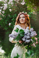 Spring beauty girl with long red hair in a white plate outdoors. Flowering tree. Romantic portrait of young woman with bouquet.