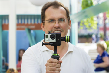 Man holds small action camera