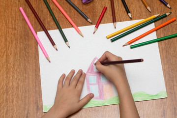 Child drawing with bright pencils on paper