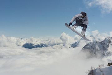 Snowboarder jumping in mountains, extreme sport.