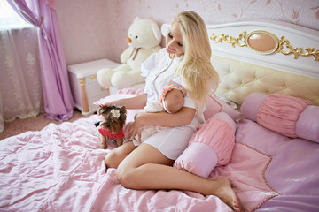 Blonde woman strokes little dog while holding her child on the a
