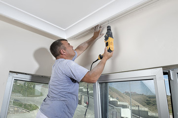 Worker Drilling a Hole on the Ceiling