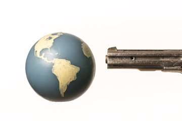 Barrel of a gun threatens the world globe.  On white background. With copy space text.