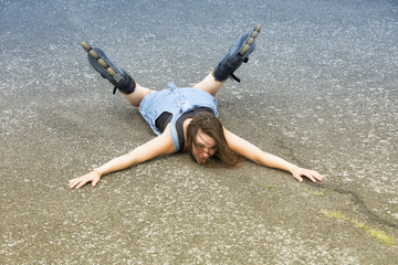 woman with rollerblades lying on asphalt after accident