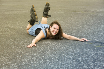 woman with rollerblades lying on the street and is laughing