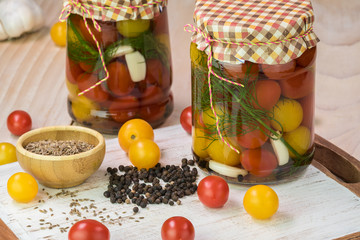 Cherry tomatoes pickles in glass jars with lid.