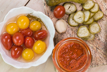 Dill pickles and cherry tomatoes pickles on a cutting board and roasted red pepper in open jar.