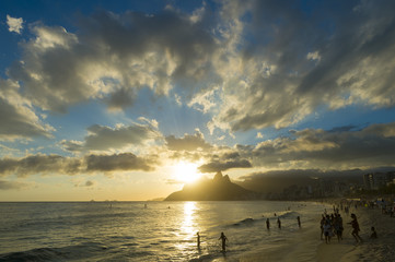 Scenic sunset view from the shore of Ipanema Beach with Two Brothers Dois Irmaos Mountain in Rio de Janeiro, Brazil