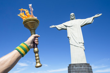 Hand of Brazilian torchbearer athlete holding sport torch next to Christ the Redeemer at Corcovado in Rio de Janeiro, Brazil