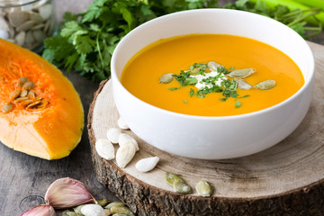 Pumpkin soup in bowl and ingredients on rustic wood