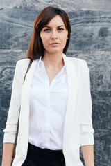 Successful businesswoman in white shirt looking away