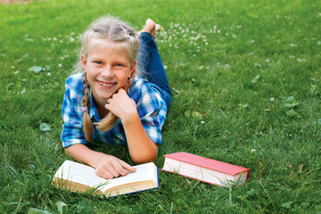 little girl is lying on her stomach reading on the grass.