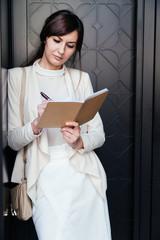 Brunette businesswoman taking notes in planner