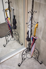 Colorful umbrella cane is hanging on the coat stand.