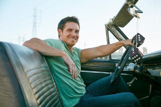 Man in convertible car looking at camera smiling, Los Angeles, California, USA