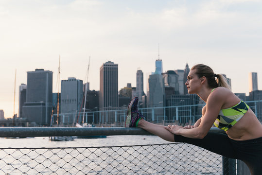 Young woman exercising outdoors, at waterfront, stretching leg, Brooklyn, New York, USA