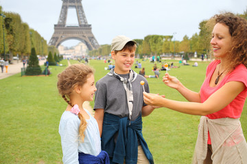 Mother, son and daughter with lollipops near the Eiffel Tower in Paris